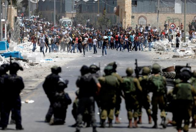 Palestinian protesters hurl stones at Israeli troops following a protest in support of Palestinian prisoners on hunger strike in Israeli jails, in the West Bank village of Beita, near Nablus May 19, 2017. REUTERS/Mohamad Torokman
