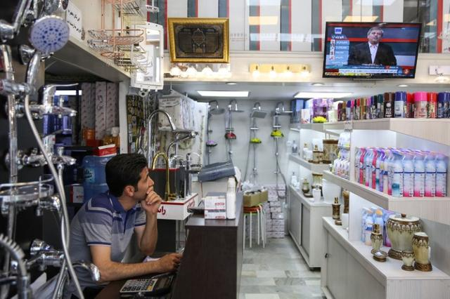 A shop keeper watches TV as he follows the presidential election results, in Tehran, Iran, May 20, 2017. TIMA via REUTERS