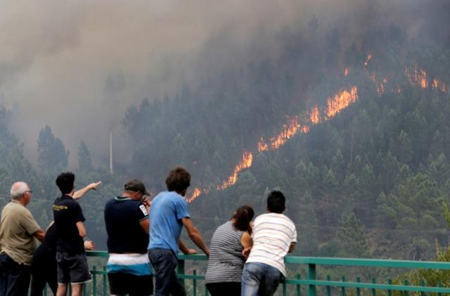 People look at fire and smoke during a forest fire in Pedrogao Grande, in central Portugal, June 18, 2017.  REUTERS/Miguel Vidal