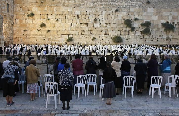 Female Jewish worshippers pray in front of the men's section at the Western Wall. Ammar Awad