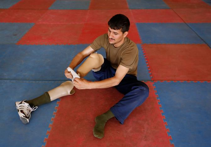 Salahuddin Zahiri 28, wounded soldier from Afghanistan's National Army (ANA) wears his prosthetic leg after his practice for Invictus Games competition, at the Kabul Military Training Centre (KMTC) in Kabul, Afghanistan July 4, 2017. Mohammad Ismail