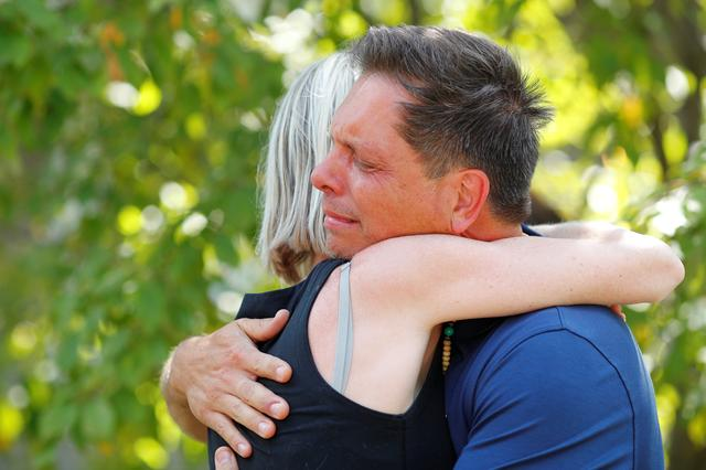 Don Damond hugs a neighbor after reading a statement about his fiance, Justine Damond who was fatally shot by Minneapolis police in Minneapolis, Minnesota, U.S., July 17, 2017. REUTERS/Adam Bettcher