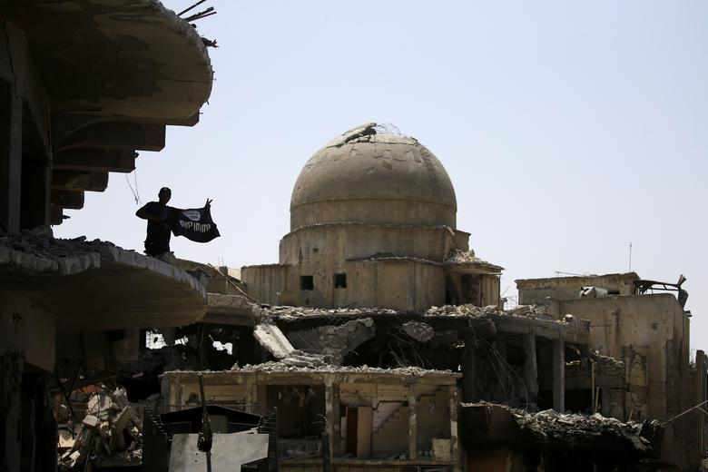 A member of Iraqi security forces holds an Islamic State flag on top of a building destroyed from clashes in the Old City of Mosul, Iraq July 10, 2017. REUTERS/Thaier Al-Sudani
