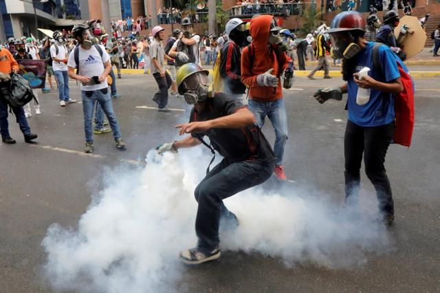 FILE PHOTO: A demonstrator prepares to throw a tear gas canister during riots at a rally against Venezuelan President Maduro's government in Caracas, Venezuela, June 7, 2017. REUTERS/Marco Bello/File Photo