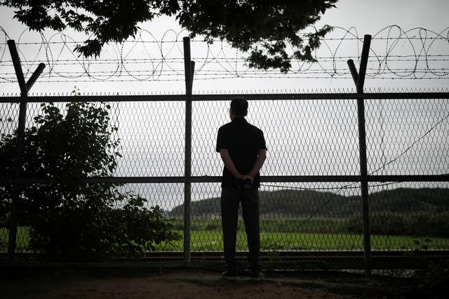 A man looks from a barbed-wire fence near the demilitarized zone separating the two Koreas in Paju, South Korea, August 10, 2017.  REUTERS/Kim Hong-Ji
