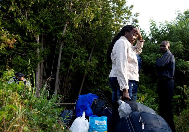 A family that stated they are from Haiti waits to enter into Canada from Roxham Road in Champlain, New York, U.S. August 11, 2017. REUTERS/Christinne Muschi
