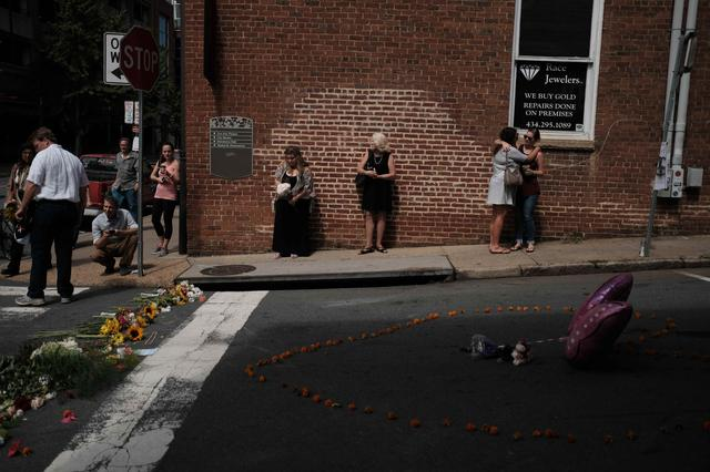 Mourners gather at a makeshift memorial at the scene of where a car plowed into counter-protesters in Charlottesville, Virginia,  August 13, 2017. REUTERS/Justin Ide