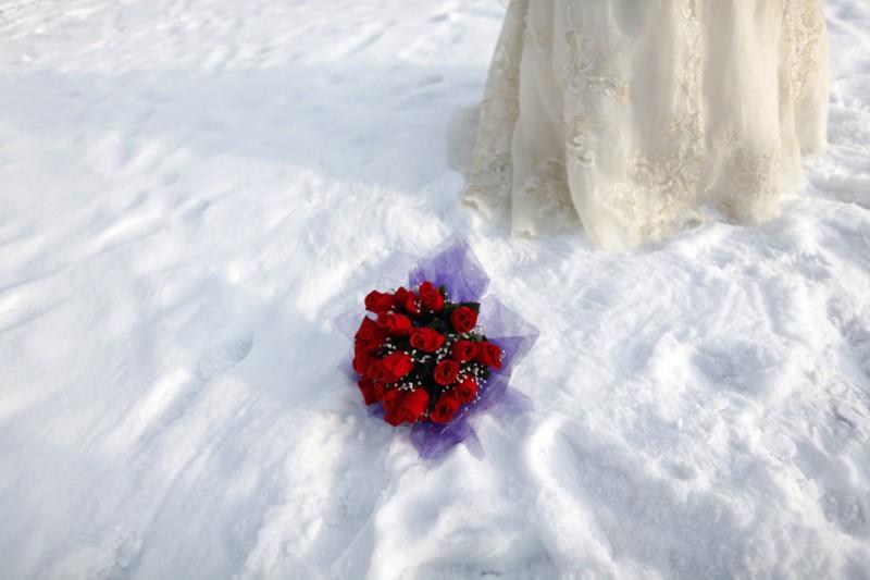 A bouquet is seen in the snow as a bride poses for a photograph in a file photo. Aly Song