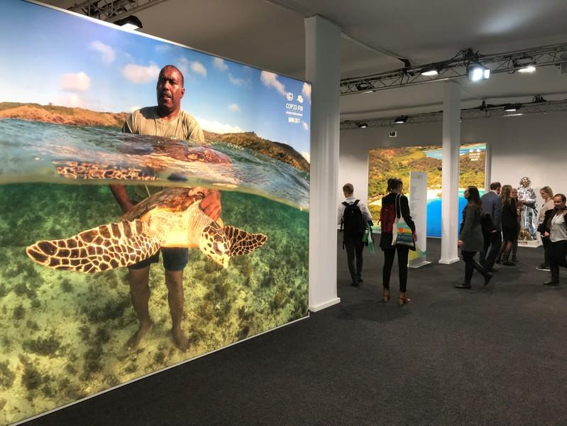 Delegates walk past a poster showing a man holding a turtle and other pictures from the Pacific Islands during the COP23 UN Climate Change Conference 2017, hosted by Fiji but held in Bonn, Germany November 10, 2017. Alister Doyle