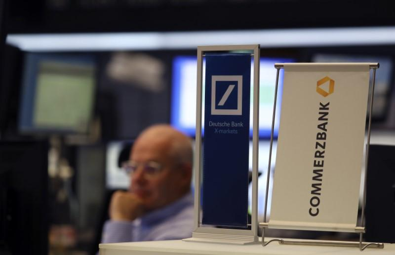 Banners of Deutsche Bank and Commerzbank are pictured in front of a trader at the stock exchange in Frankfurt, Germany, September 30, 2016. Kai Pfaffenbach