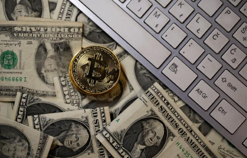 A bitcoin (virtual currency) coin placed on Dollar banknotes, next to computer keyboard, is seen in this illustration picture, November 6, 2017. Dado Ruvic/Illustration