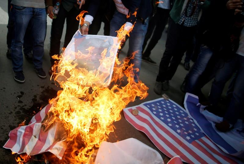 Palestinian protesters burn a poster depicting U.S. President Donald Trump and a representation of a U.S. flag during a protest against Trump's decision to recognize Jerusalem as the capital of Israel, in Gaza City December 7, 2017. Mohammed Salem