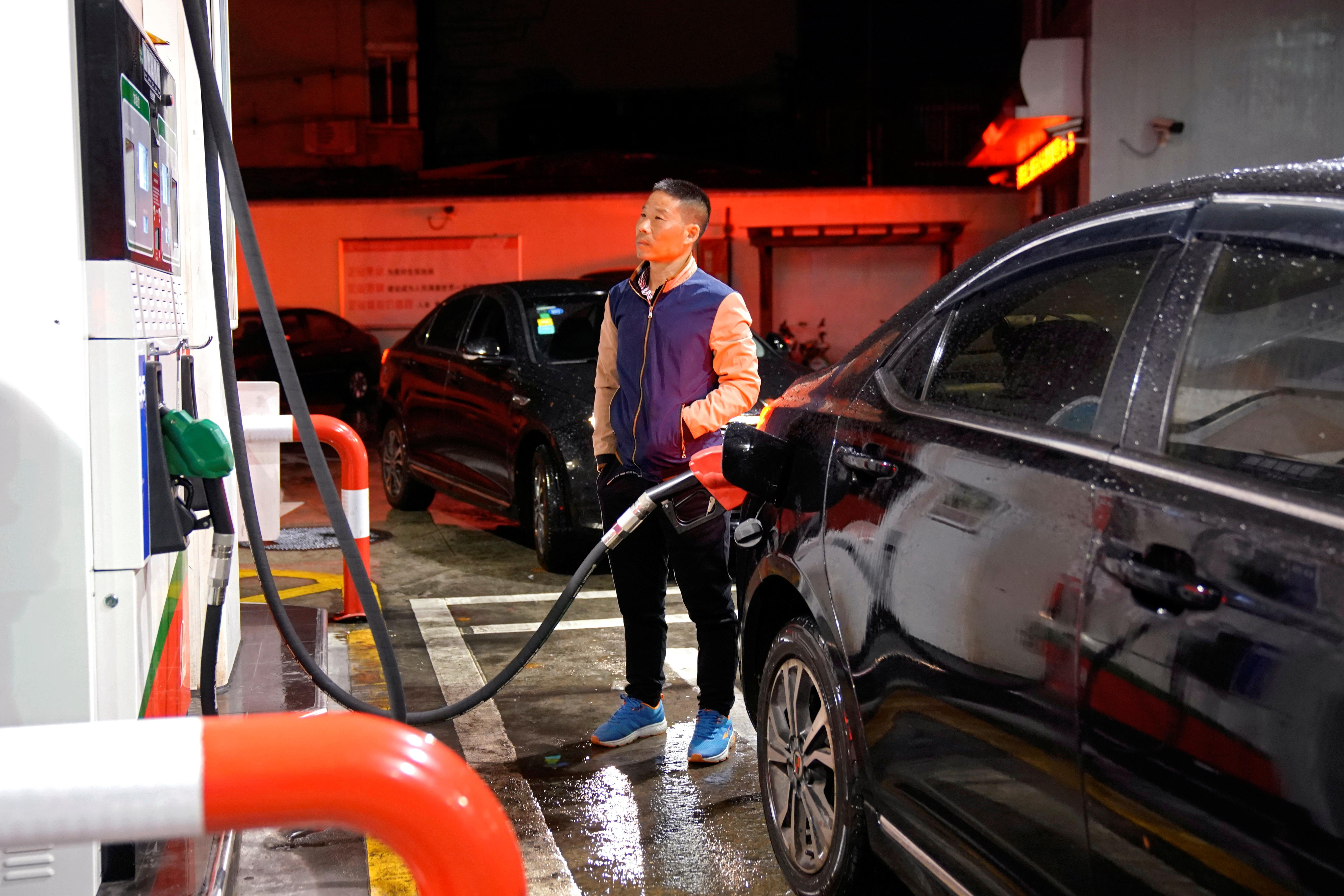 A driver looks at the price as he fills the tank of his car at a gas station in Shanghai, China November 17, 2017. Aly Song