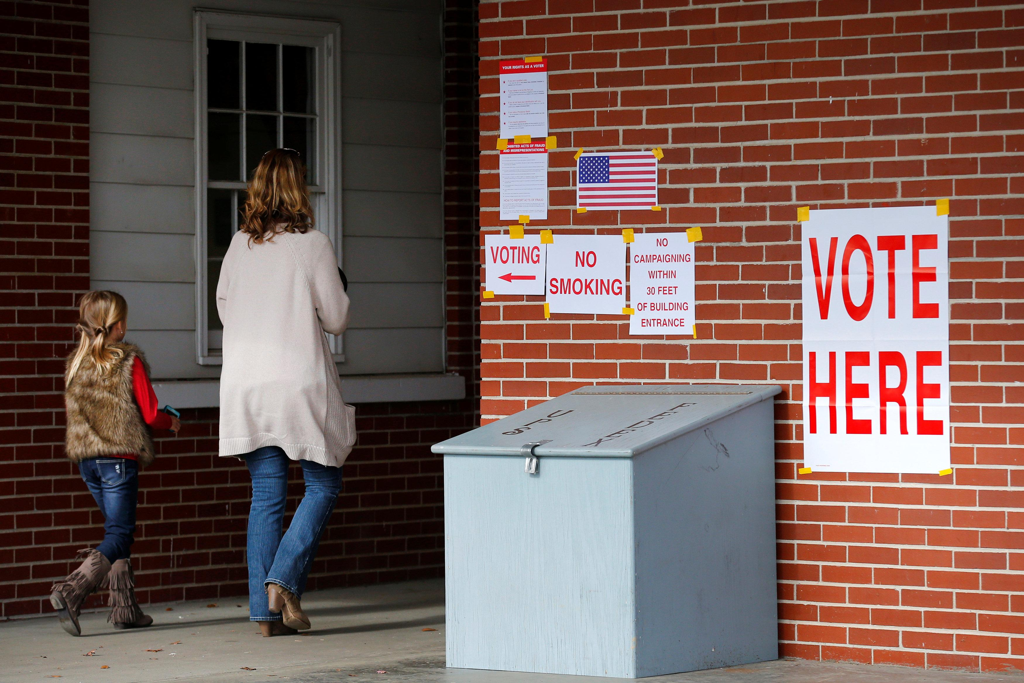 Anna Atkinson walks into a polling station with her 8-year-old daughter Tori, in Gallant, Alabama, U.S., December 12, 2017.  Jonathan Bachman