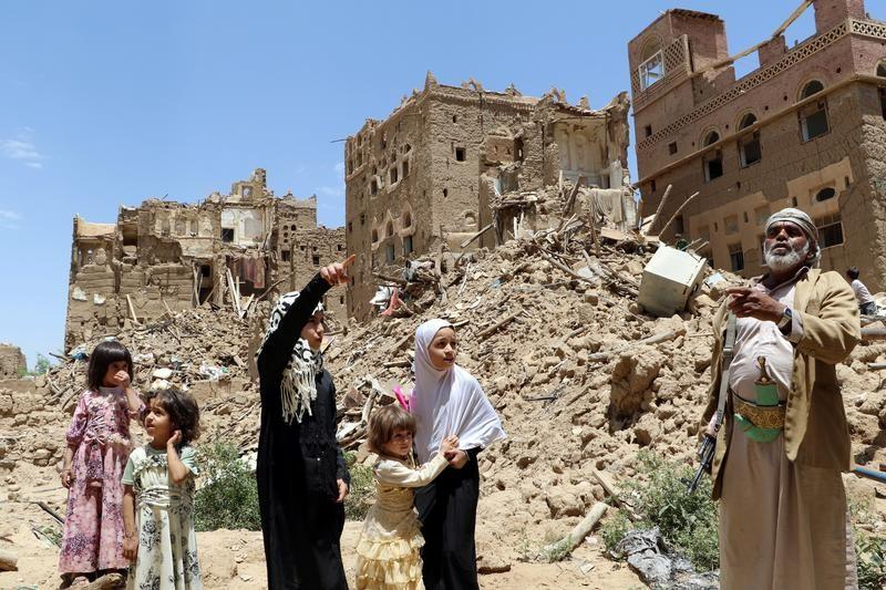 People stand outside houses destroyed by Saudi-led air strikes in the northwestern city of Saada, Yemen September 5, 2017. Naif Rahma