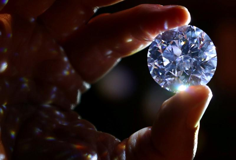 An assistant holds a 102.34 carat white diamond at Sotheby's auction house in London, Britain February 8, 2018. Hannah McKay