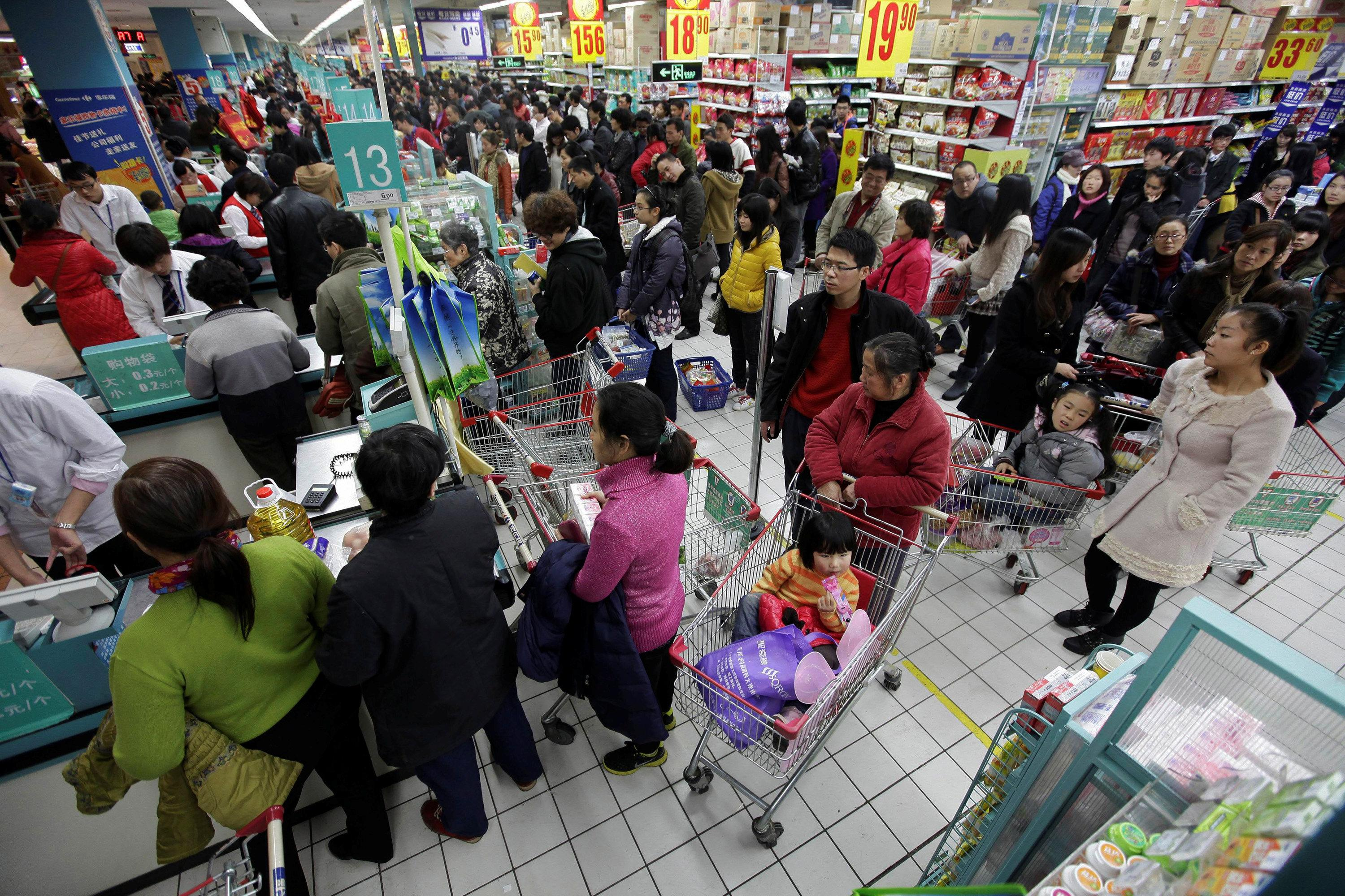 Customers queue to pay as they shop at a Carrefour supermarket in Wuhan, Hubei province December 3, 2011.  Stringer