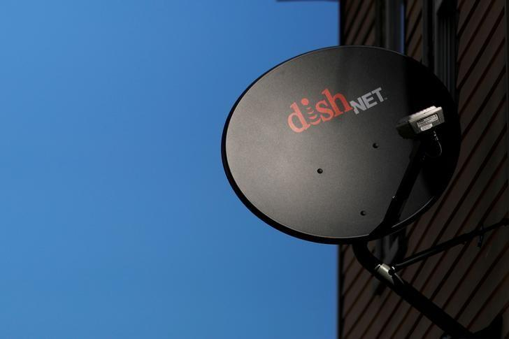 A Dish Network receiver hangs on a house in Somerville, Massachusetts, U.S. on February 21, 2017.   Brian Snyder