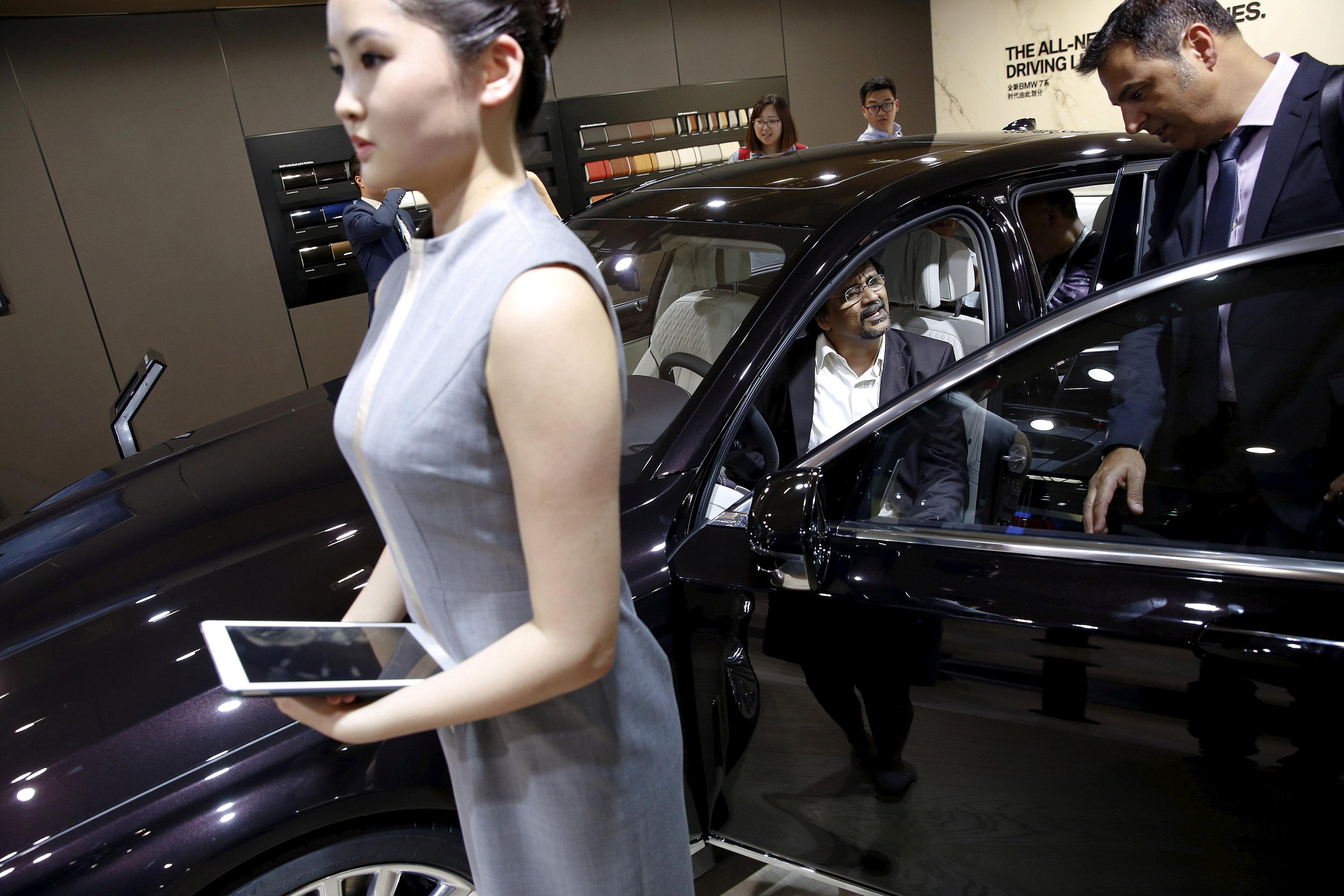 People check out the new BMW M760Li xDrive as it is presented during the Auto China 2016 auto show in Beijing April 25, 2016. Damir Sagolj