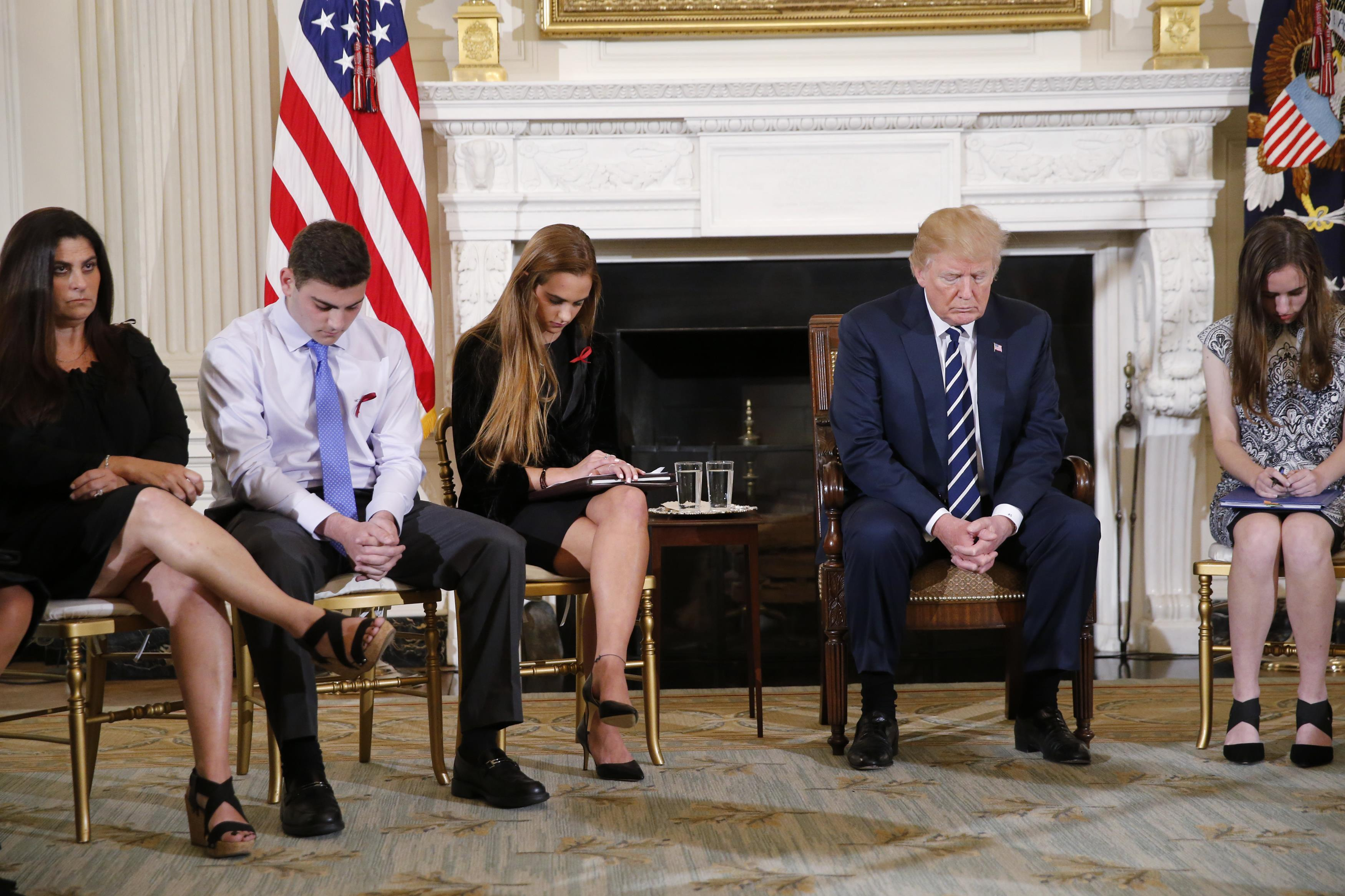 U.S. President Donald Trump bows his head during a prayer as he sits between Marjory Stoneman Douglas High School shooting survivors and students Jonathan Blank, his mother Melissa Blank, Julia Cordover and Carson Abt (R), as the president hosts a listening session with high school students and teachers to discuss school safety at the White House in Washington, U.S., February 21, 2018. Jonathan Ernst