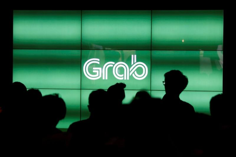People wait for the start of ride-hailing company Grab's fifth anniversary news conference in Singapore June 6, 2017. Edgar Su
