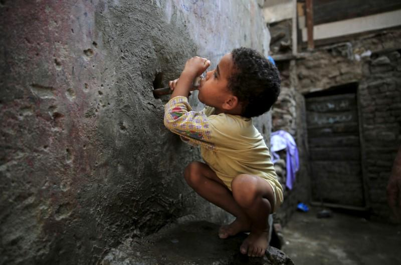 Five-year-old Karkar tries to drink water from a faucet near his home in the Eshash el-Sudan slum in the Dokki neighbourhood of Giza, south of Cairo, Egypt September 2, 2015. Amr Abdallah Dalsh