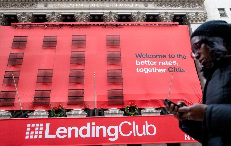 A woman looks at her phone as she passes by a LendingClub banner on the facade of the the New York Stock Exchange December 11, 2014.   Brendan McDermid