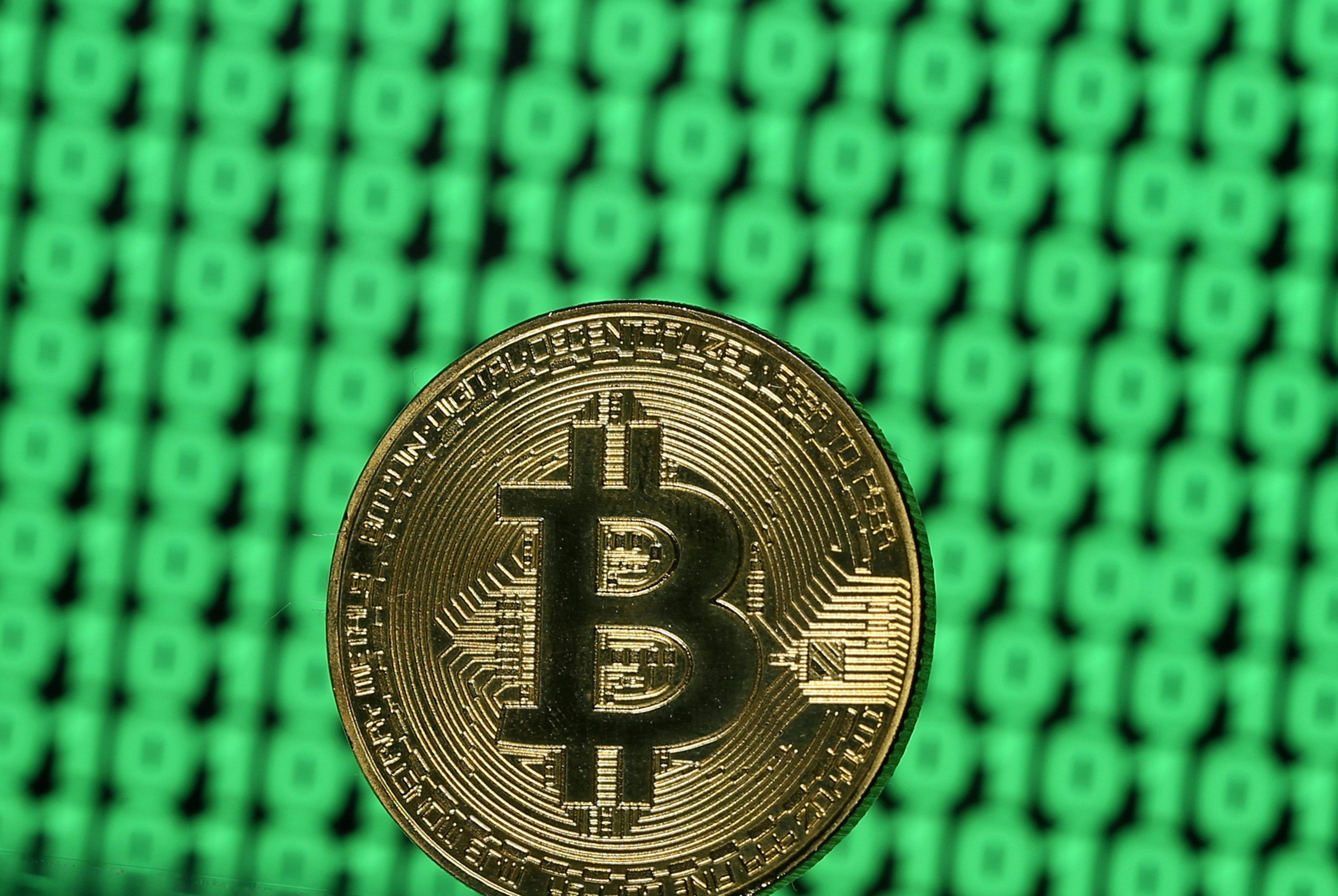 A token of the virtual currency Bitcoin is seen placed on a monitor that displays binary digits in this illustration picture, December 8, 2017.  Dado Ruvic/