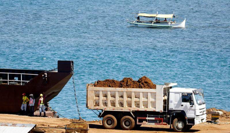 A truck loads rocks and soil containing nickel-ore minerals into a barge in the mining town of Sta Cruz Zambales in northern Philippines February 8, 2017.    Erik De Castro