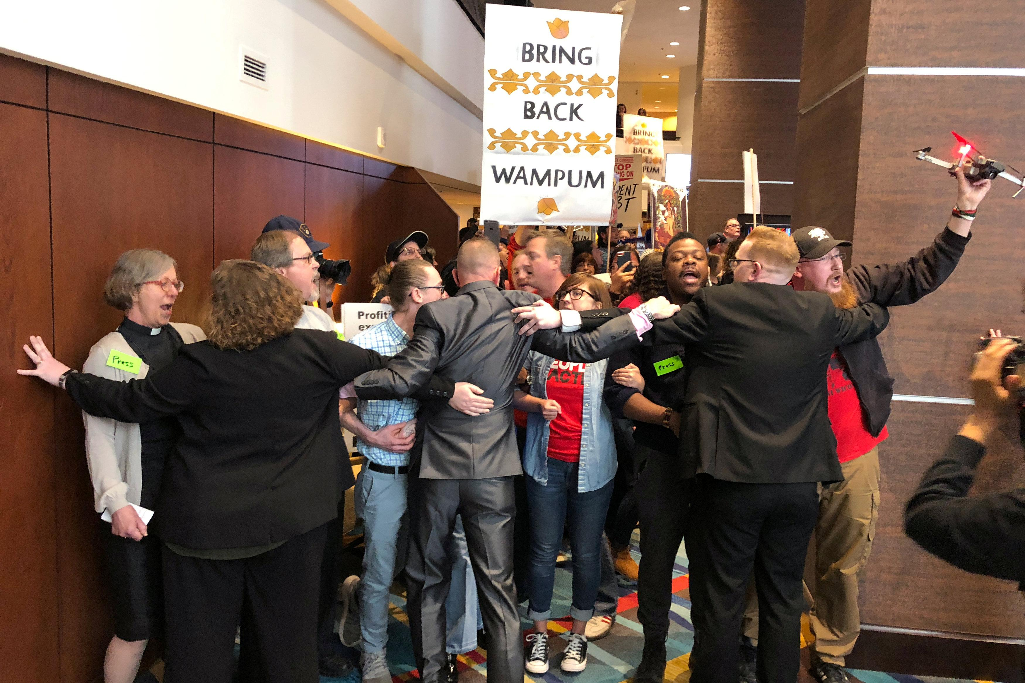 Guards hold back about 100 protestors gathered in a hotel lobby outside Wells Fargo & Co's annual shareholder meeting in Des Moines, Iowa, U.S., April 24, 2018.    Ross Kerber
