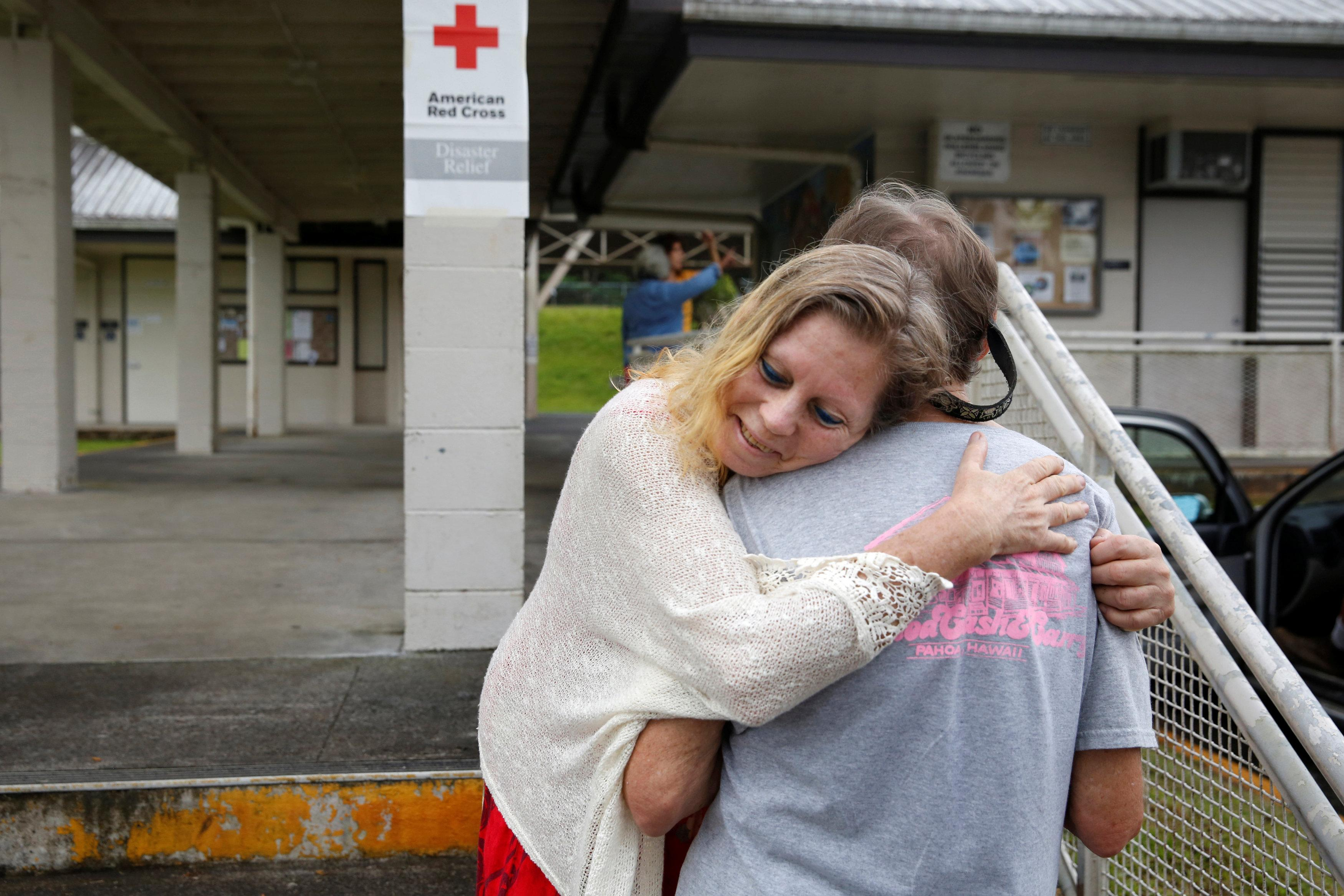 Carolyn McNamara, 70, hugs her neighbor Paul Campbell, 68, at an evacuation center in Pahoa after moving out of their homes in the Puna community of Leilani Estates after the Kilauea Volcano, one of five on the island, erupted on Thursday after a series of earthquakes over the last couple of days, in Hawaii, U.S., May 4, 2018. Terray Sylvester