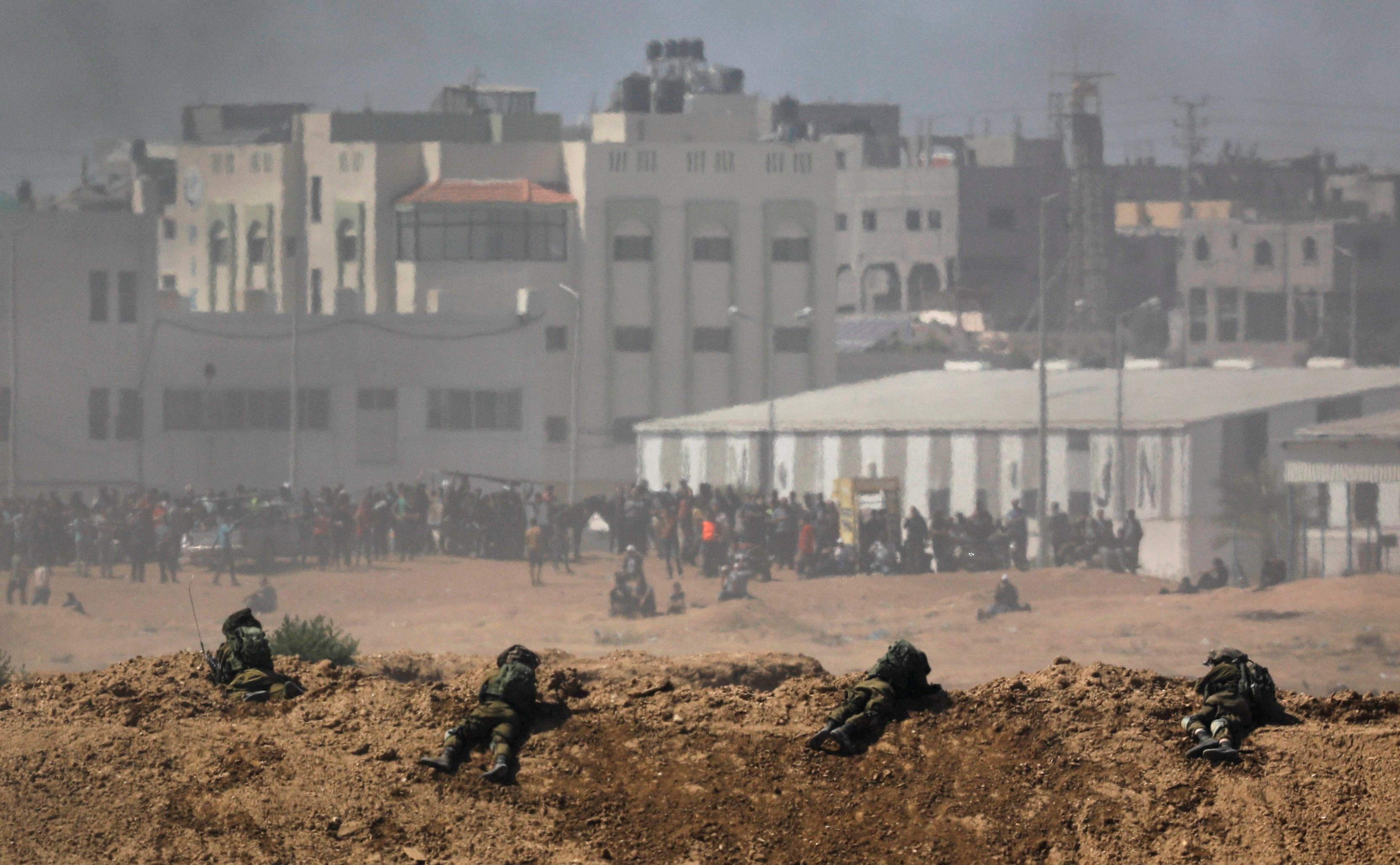 Smoke rises as Israeli soldiers are seen on the Israeli side of the border with the Gaza Strip, Israel, May 14, 2018.  Amir Cohen
