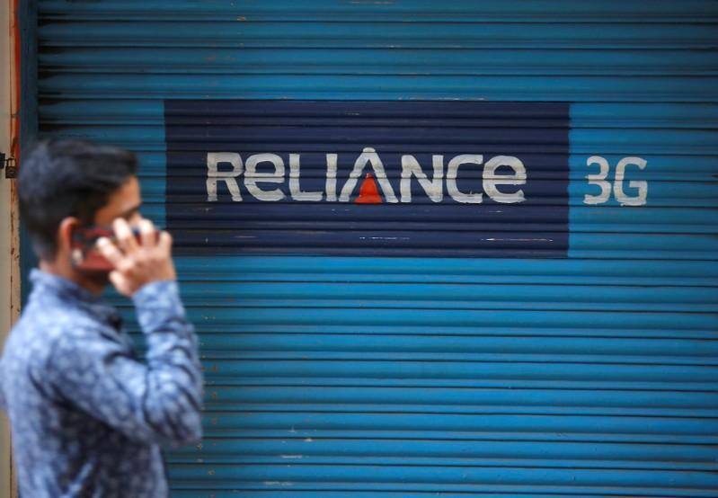 A man speaks on his mobile phone as he walks past a closed shop painted with an advertisement of Reliance Communications in Mumbai, India, January 29, 2018. Shailesh Andrade/File photo