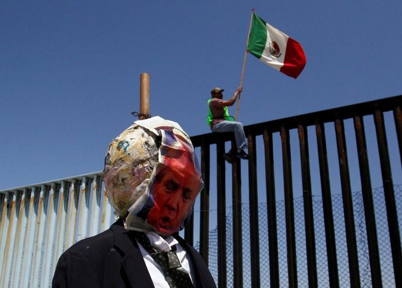 A demonstrator holds a Mexican flag while sitting on the border fence between Mexico and the U.S., near an effigy depicting U.S. President Donald Trump, during a protest against the immigration policies of Trump's government, in Tijuana, Mexico May 10, 2018. Jorge Duenes