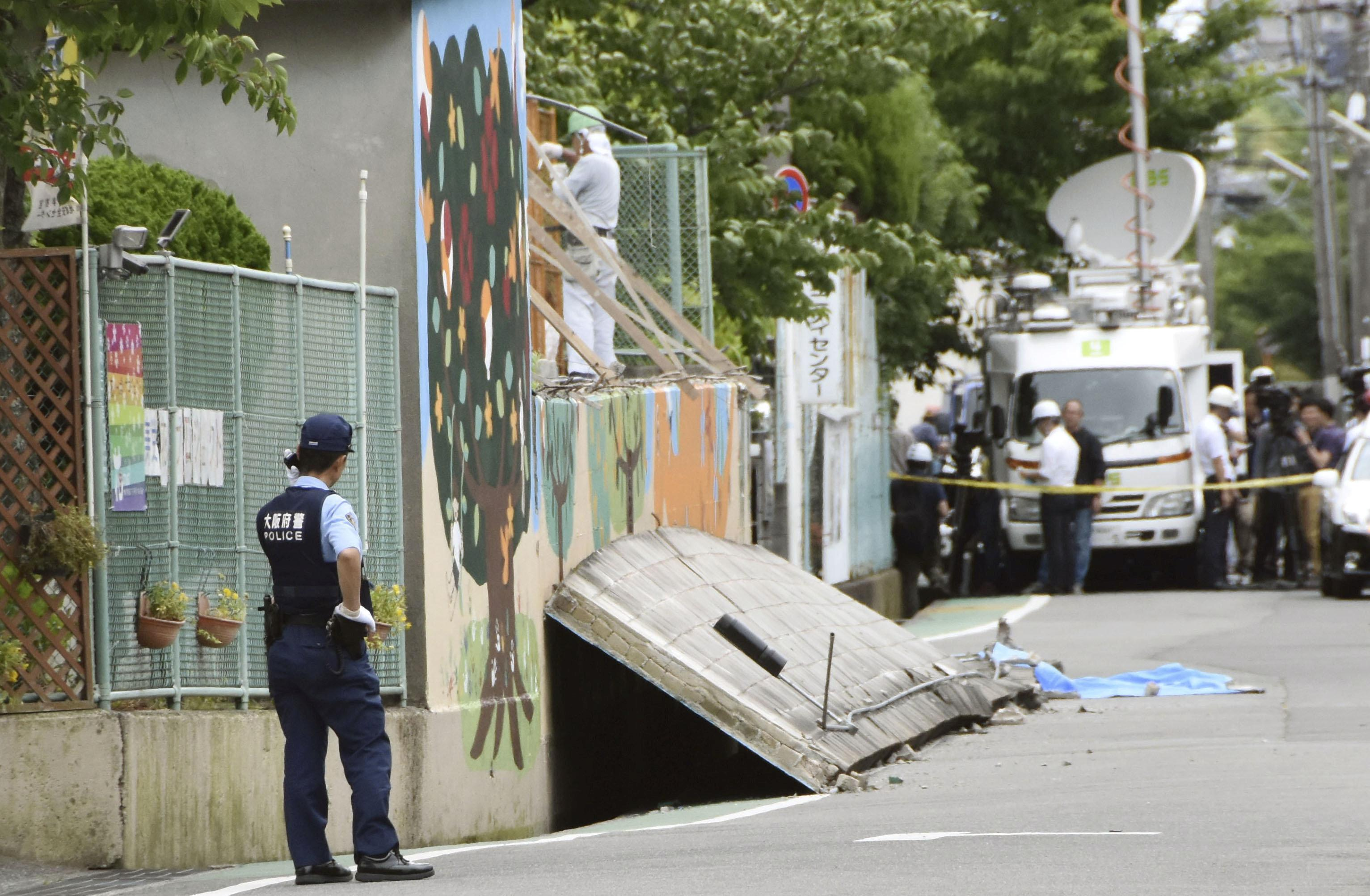 A police officer stands guard at the site where a girl was killed by fallen wall caused by an earthquake at an elementary school in Takatsuki, Osaka prefecture, western Japan, in this photo taken by Kyodo June 18, 2018.   Mandatory credit Kyodo/via