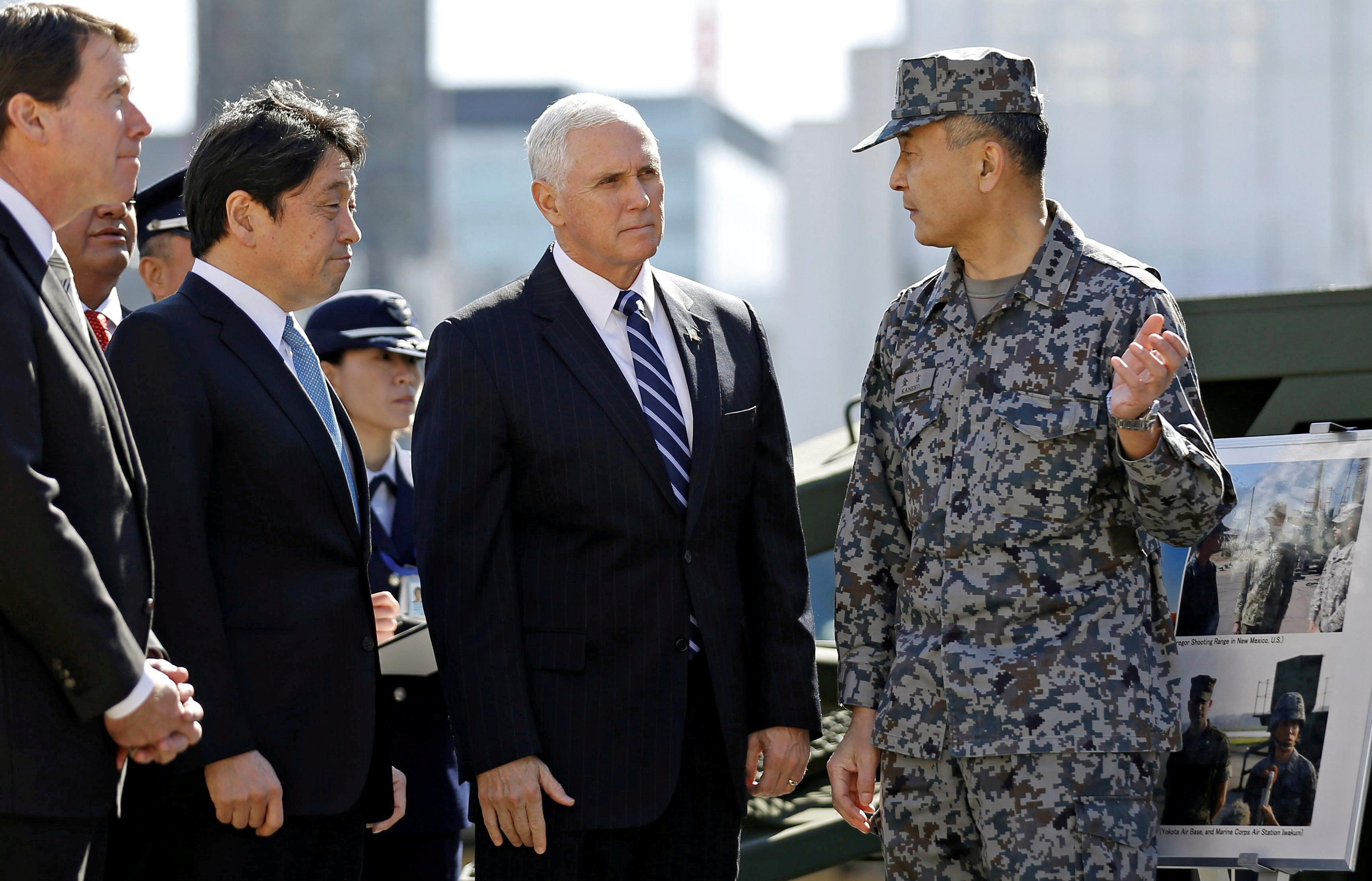 U.S. Vice President Mike Pence speaks with a Japanese Ground Self-Defense Force officer as he inspects PAC-3 missile interceptors with Japan's Defense Minister Itsunori Onodera at the Defense Ministry in Tokyo, Japan February 7, 2018.  Toru Hanai
