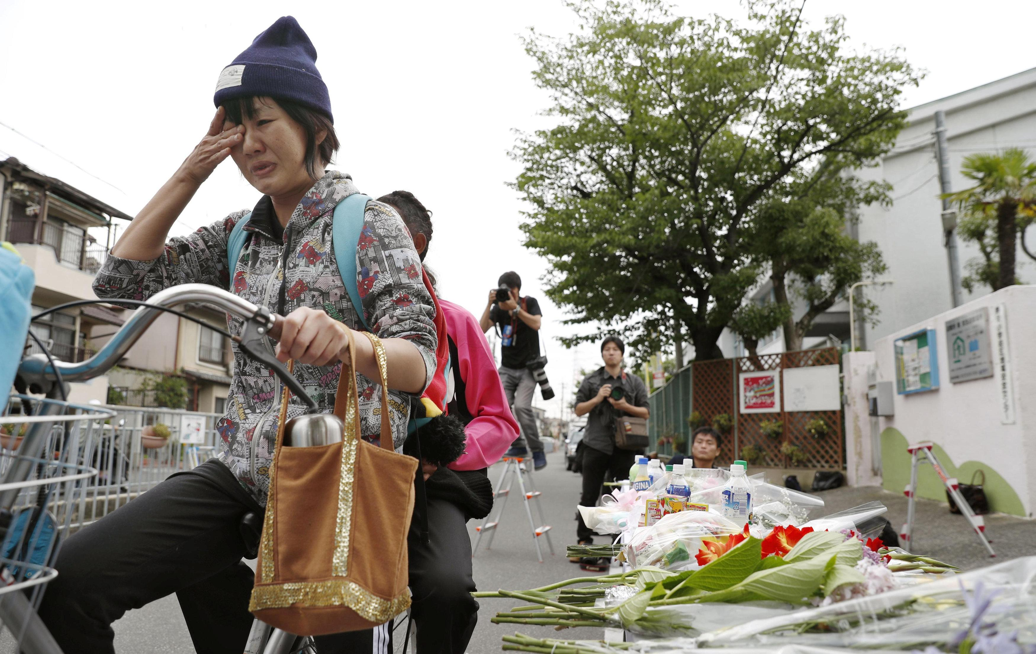 A woman in a bicycle cries in front of floral tributes to a victim of yesterday's earthquake in Takatsuki, Osaka prefecture, western Japan, in this photo taken by Kyodo June 19, 2018. Mandatory credit Kyodo/via