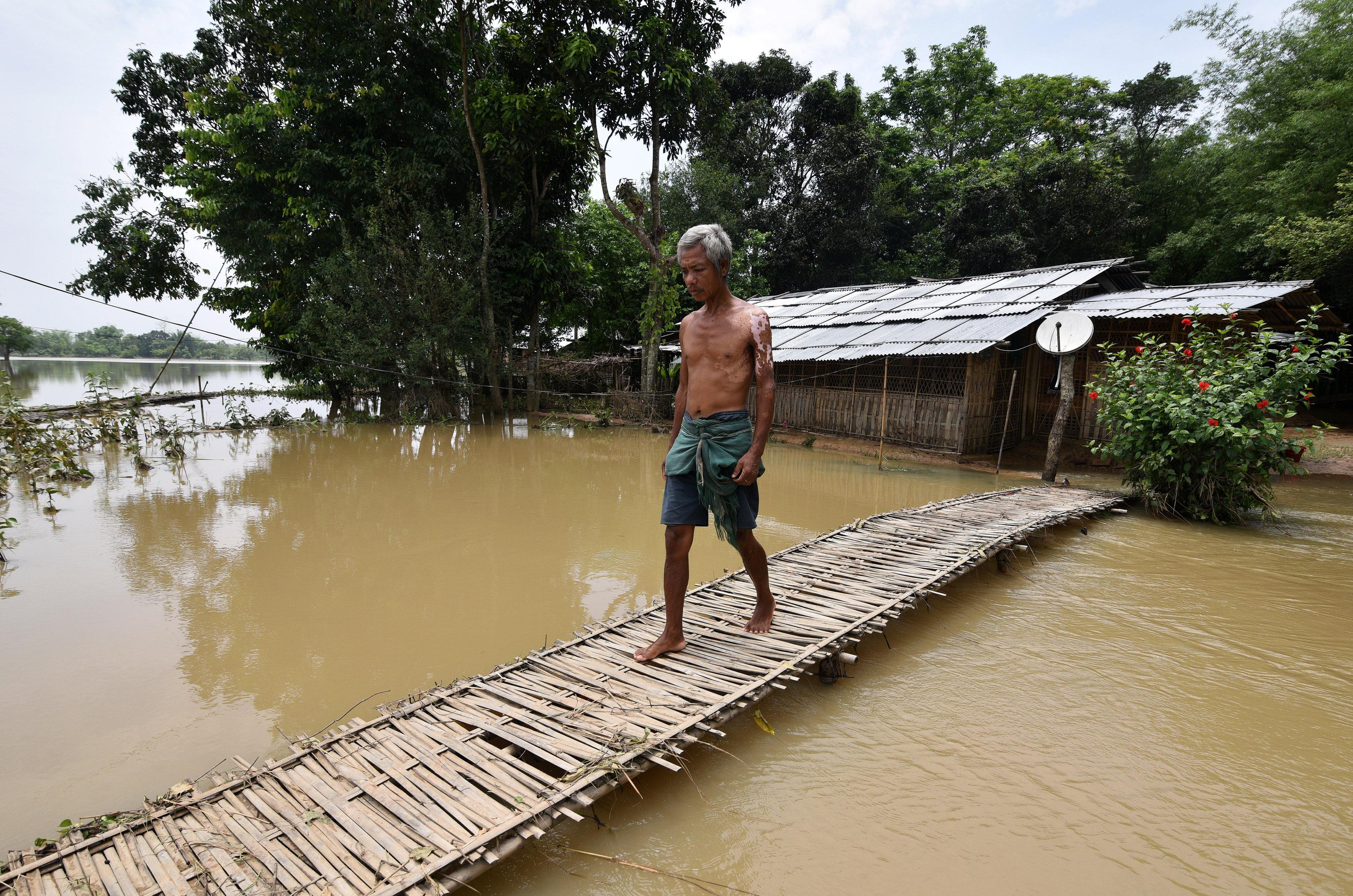 A man uses a makeshift bamboo bridge to cross a flooded area at a village in Nagaon district, in the northeastern state of Assam, India, June 19, 2018. Anuwar Hazarika