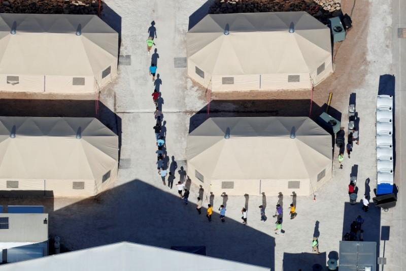 "Immigrant children, many of whom have been separated from their parents under a new ""zero tolerance"" policy by the Trump administration, are shown walking in single file between tents in their compound next to the Mexican border in Tornillo, Texas, U.S. June 18, 2018. Picture taken June 18, 2018. Mike Blake"