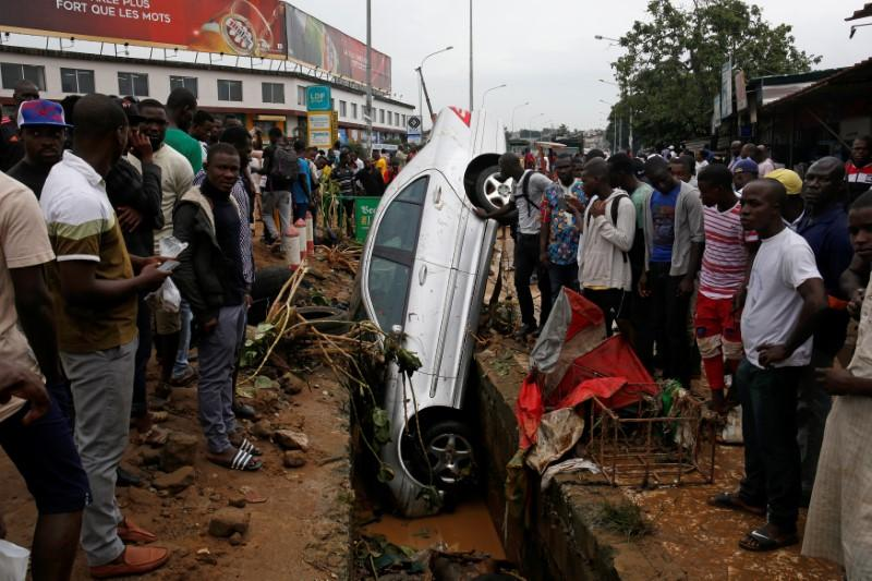 People look at a car in a sewer after a flood in Abidjan, Ivory Coast, June 19, 2018. Luc Gnago