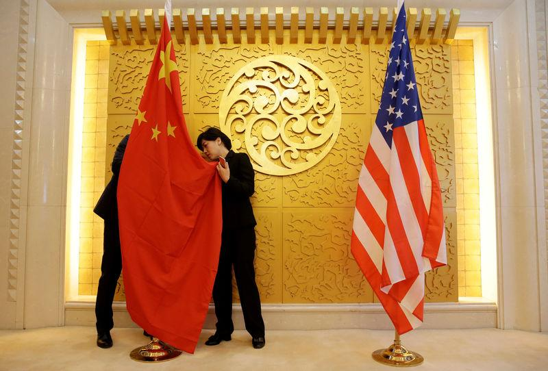 Staff members set up Chinese and U.S. flags for a meeting between Chinese Transport Minister Li Xiaopeng and U.S. Secretary of Transportation Elaine Chao at the Ministry of Transport of China in Beijing, China April 27, 2018. Jason Lee/Pool