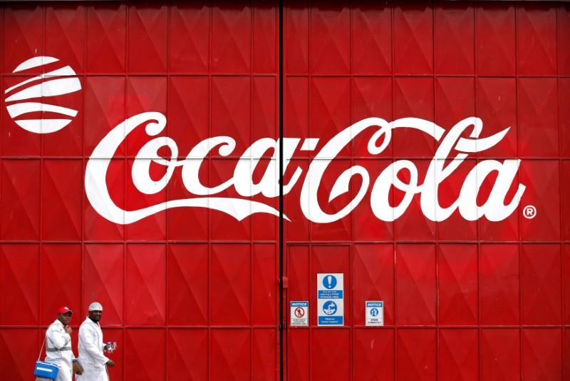 Workers walk past a Coca Cola logo painted on a gate at a Coca Cola factory in Nairobi, Kenya, June 7, 2018. Baz Ratner