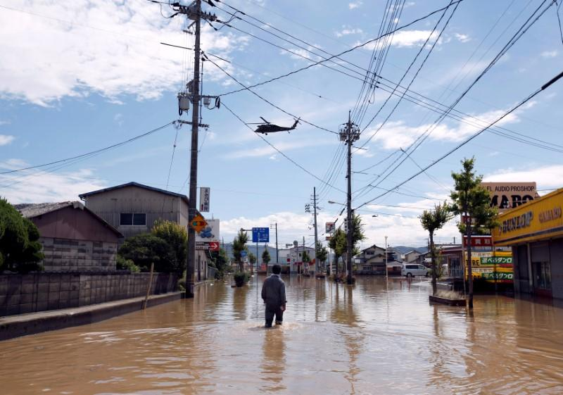 A man makes his way in a flooded area in Mabi town in Kurashiki, Okayama Prefecture, Japan, July 8, 2018. Issei Kato