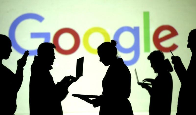 Silhouettes of laptop and mobile device users are seen next to a screen projection of Google logo in this picture illustration taken March 28, 2018.  Dado Ruvic/Illustration