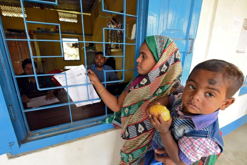 A woman carrying her son arrives to check her name on the draft list of the National Register of Citizens (NRC) at an NRC center in Chandamari village in Goalpara district in the northeastern state of Assam, India, January 2, 2018.  Anuwar Hazarika