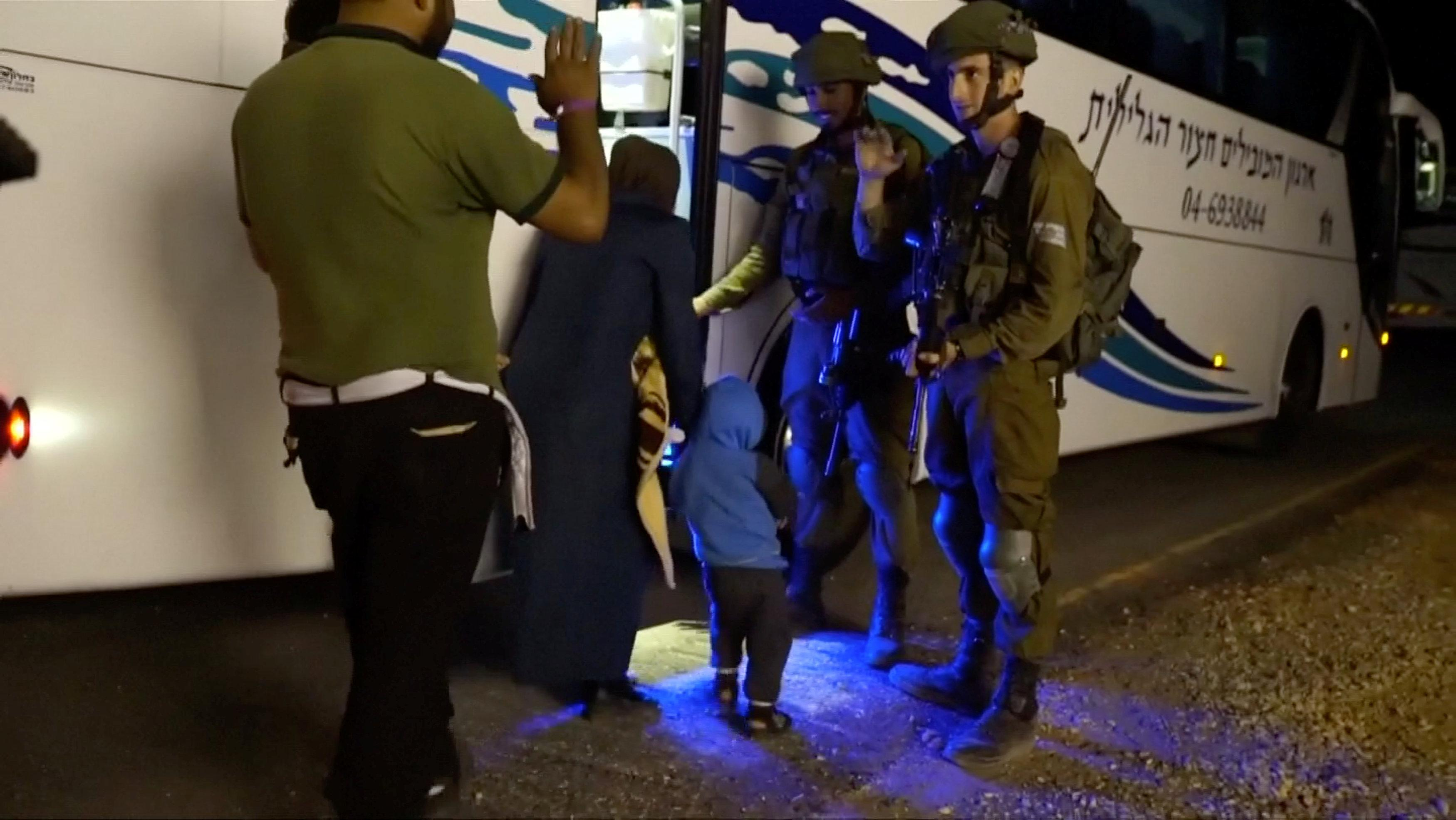 People walk past Israeli soldiers as they board a bus during the Syria Civil Defence, also known as the White Helmets, extraction from the Golan Heights, Israel in this still image taken from video, provided by the Israeli Army July 22, 2018. Israeli Army Handout via