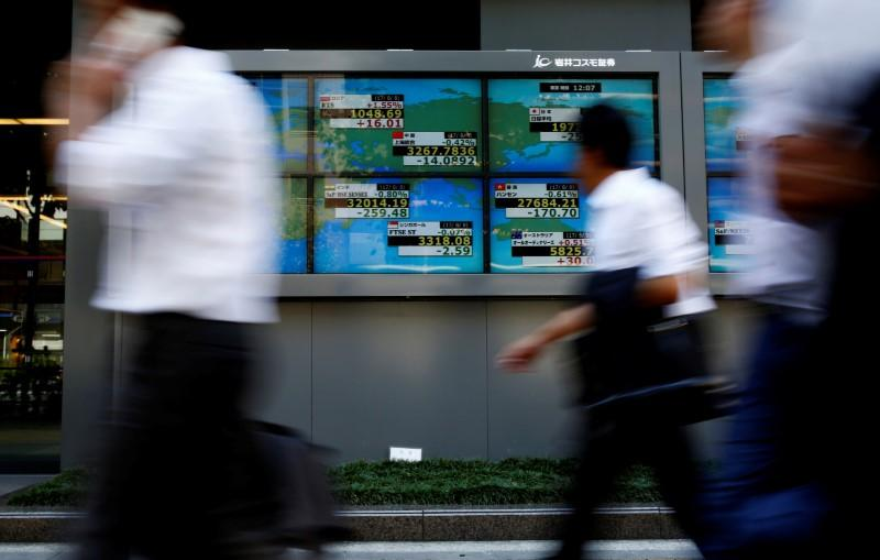 People walk past an electronic board showing Japan