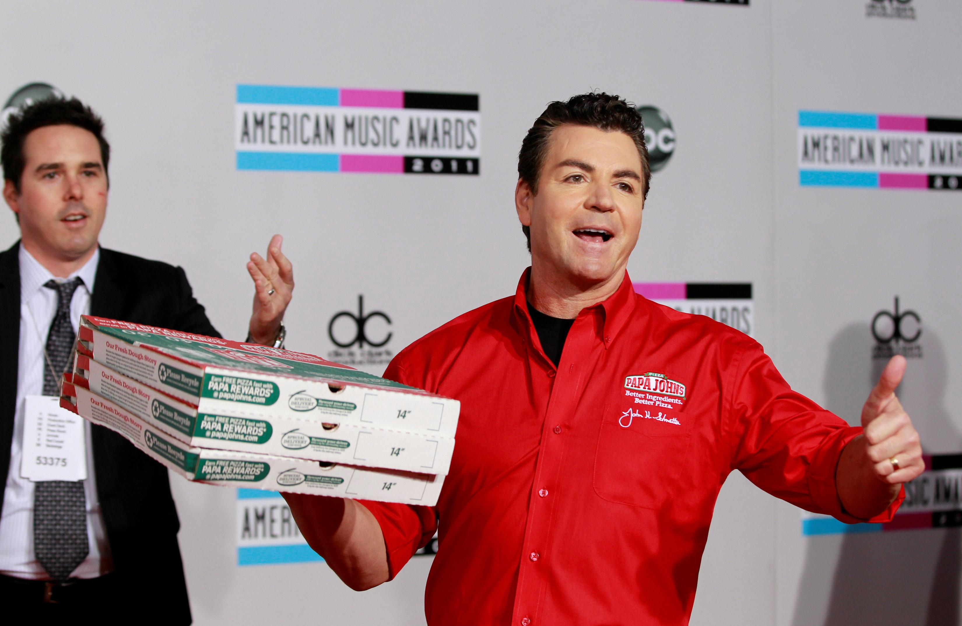 John Schnatter (R), founder and chief executive of Papa John's Pizza, arrives at the 2011 American Music Awards in Los Angeles November 20, 2011. Danny Moloshok