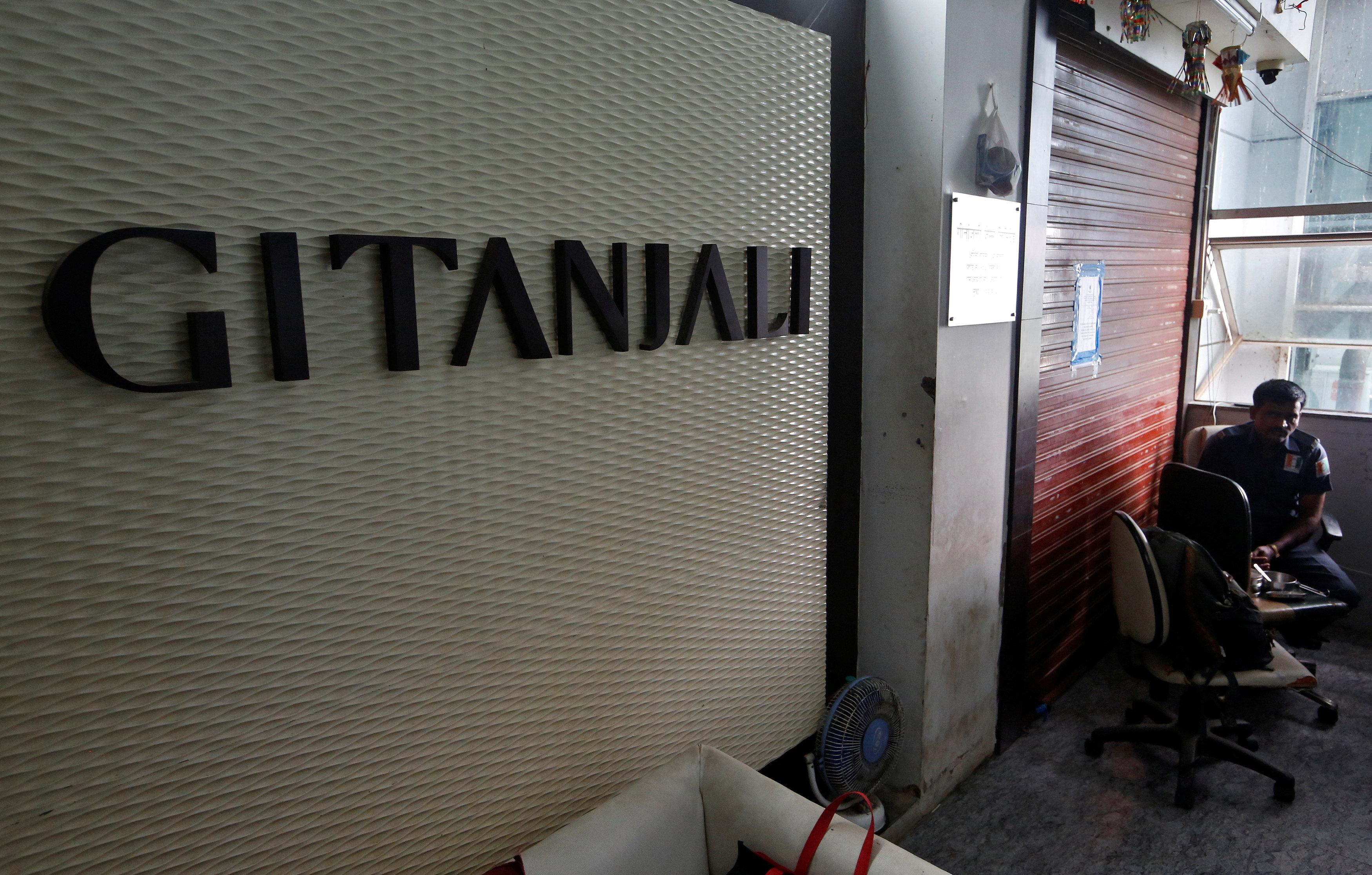 A security guard sits beside a sealed office of Gitanjali jewellers in Mumbai, India, July 23, 2018. Francis Mascarenhas
