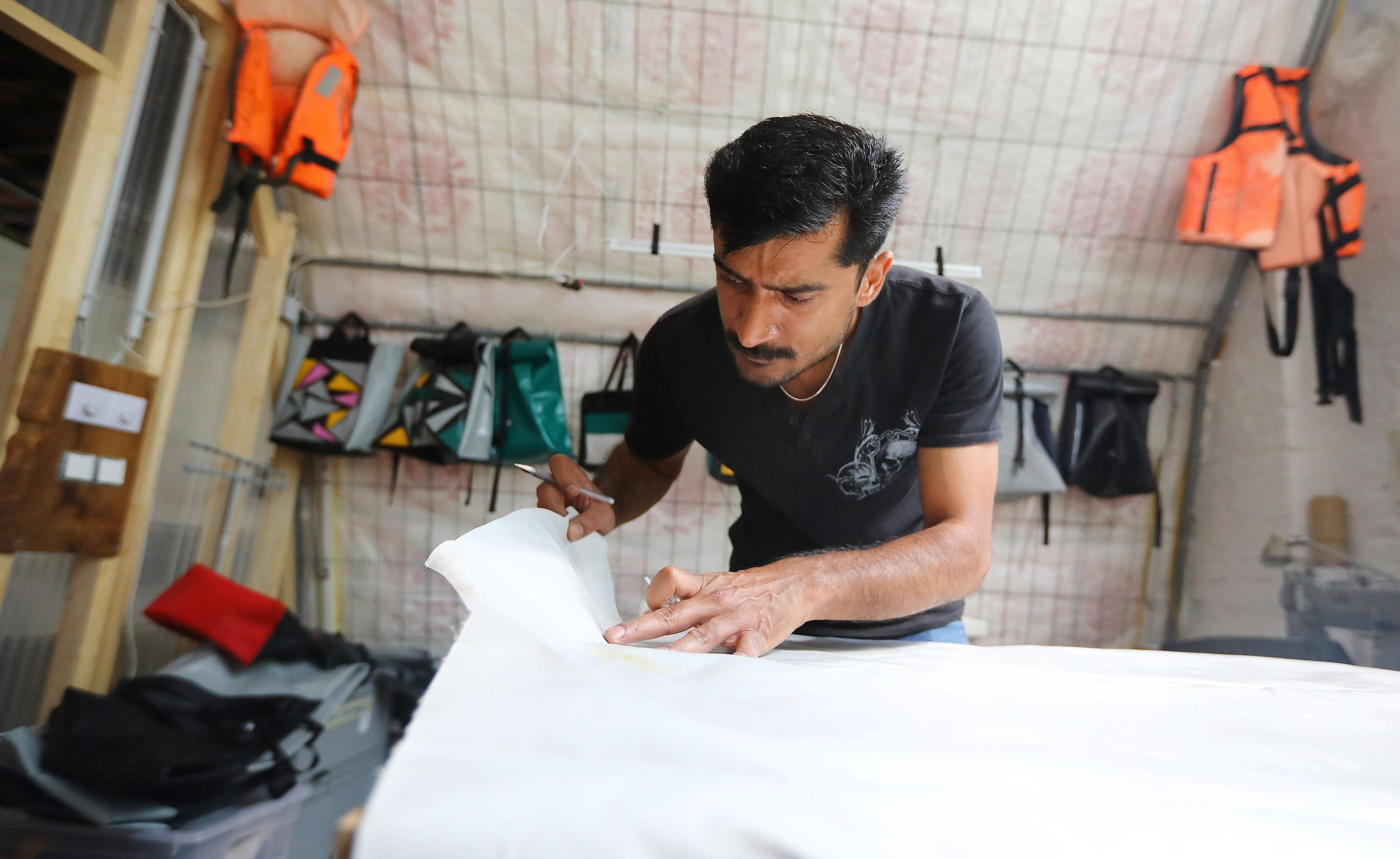 Migrant Abid Ali from Pakistan works as tailor and designer at the non-profit organization Mimycri, which recycles parts of a discarded dinghies into bags, in Berlin, Germany, July 23, 2018. Hannibal Hanschke